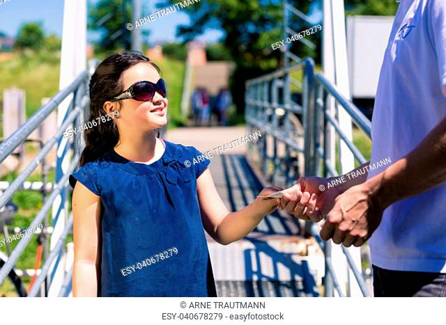 Little girl with sunglasses entering boat and buying ticket from boatman