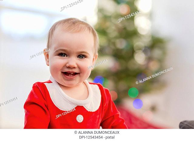 Portrait of a toddler in her festive Christmas outfit in front of the Christmas tree; Langford, British Columbia, Canada