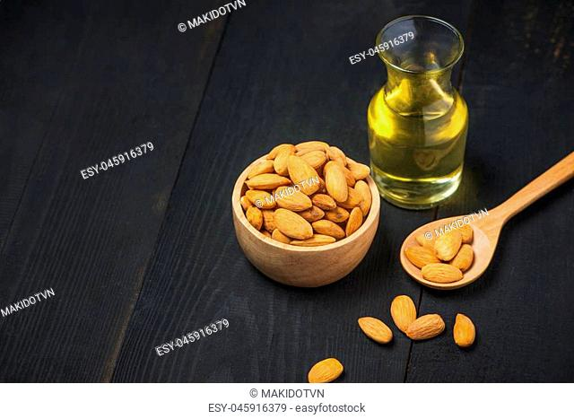 Almond oil in bottle with almonds on black wooden table
