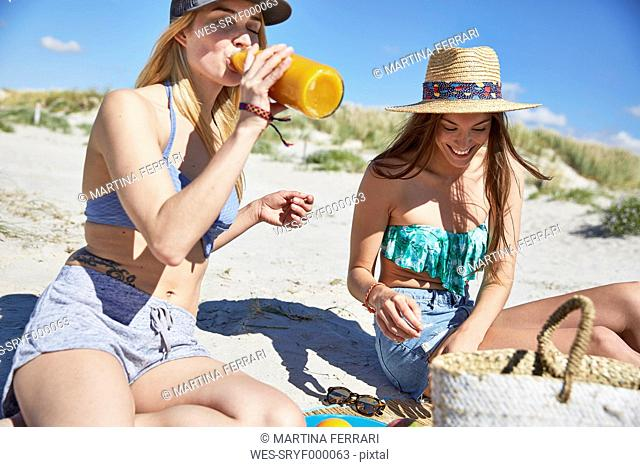 Young woman with friend on the beach drinking juice from bottle