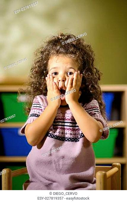 Portraits of children, 3 years old female with curly hair looking at camera in kindergarten with worried expression