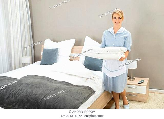 Young Female Housekeeper Holding Stack Sheet In Hotel Room