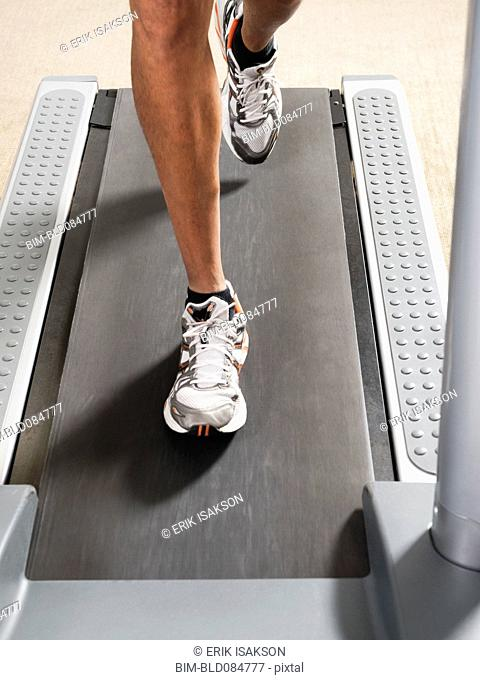 Mixed race man's legs running on treadmill