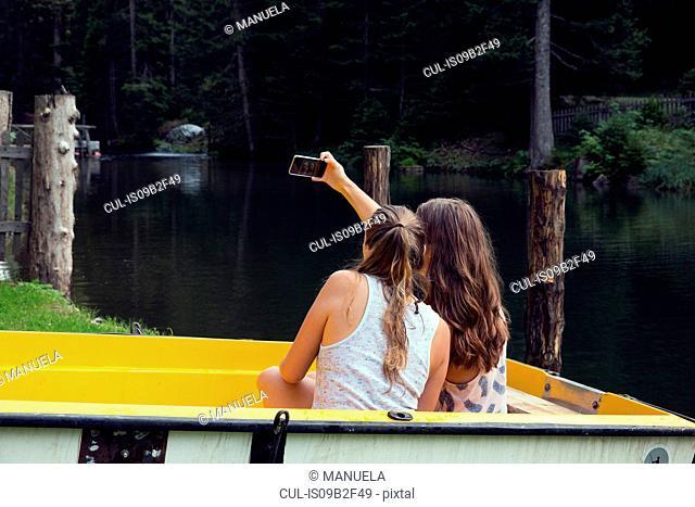 Two young female friends taking smartphone selfie in rowing boat, Sattelbergalm, Tirol, Austria