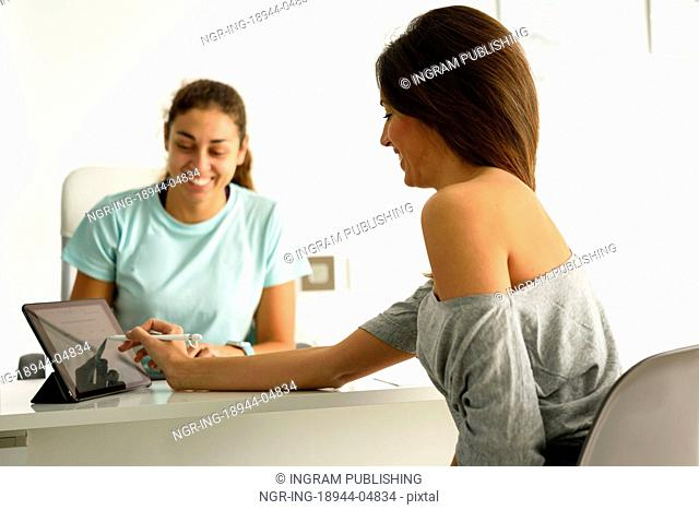 Woman accepting and signing her diagnosis with female physiotherapist. Brunette patient having consultation in physiotherapy center