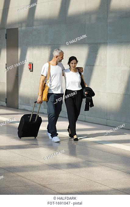Business couple with wheeled luggage talking walking by wall at airport