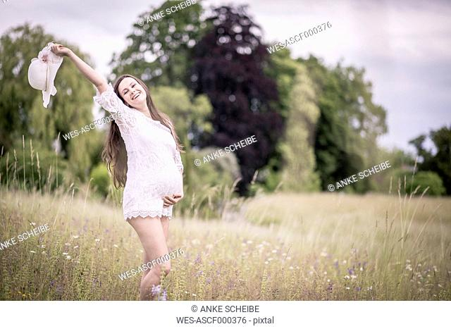 Happy pregnant woman standing on a meadow holding her belly