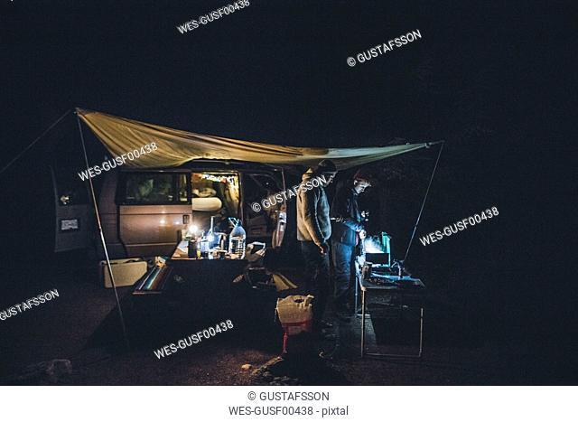 Canada, British Columbia, two men cooking under tarp at minivan at night