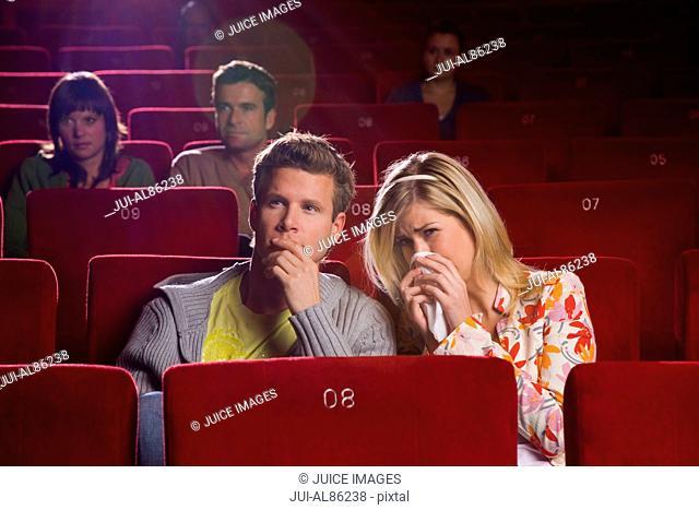 Sad couple in movie theater