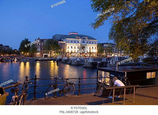 Man sitting on a bench at the riverside, Carre Theatre in the background, Amsterdam, Netherlands