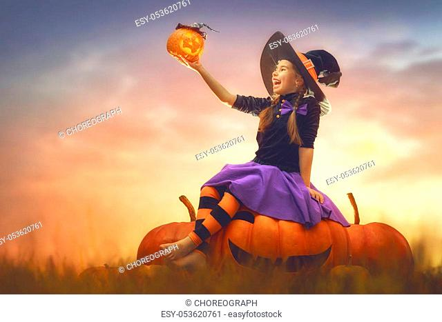 Happy Halloween! Cute little witch with pumpkins. Beautiful young child girl in costume outdoors