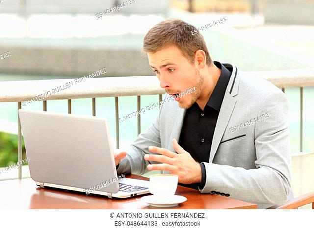 Amazed businessman receiving good news sitting in a coffee shop