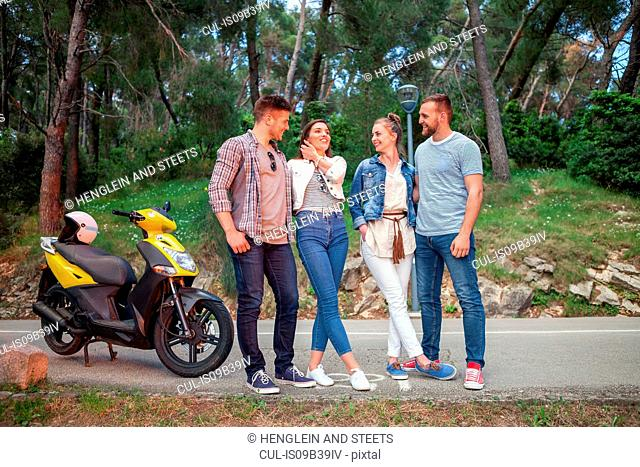 Two couples with moped chatting on rural road, Split, Dalmatia, Croatia