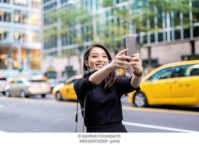 USA, New York City, Manhattan, portrait of smiling young woman taking selfie with smartphone