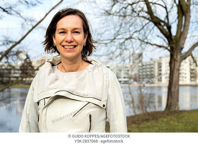 The Hague, Netherlands. Portrait of an happily smiling caucasian woman in a park