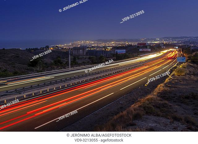Car lights and vehicle traffic at dusk, Mediterranean highway. Fuengirola, Malaga province Costal del Sol. Andalusia, Southern Spain. Europe