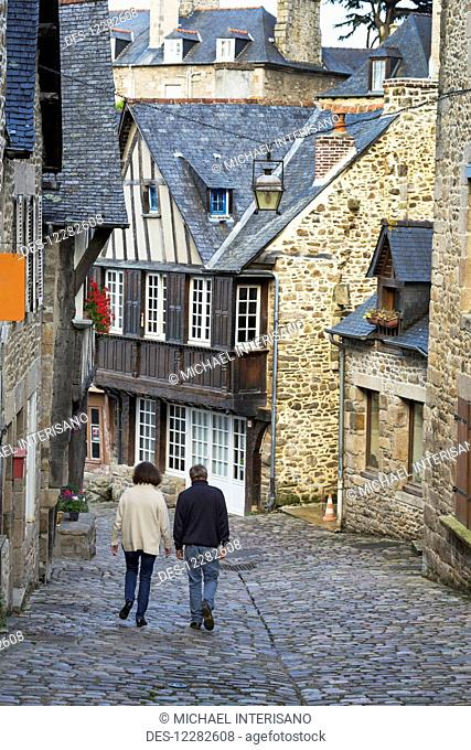 Couple walking down a cobblestone road framed with old stone buildings; Dinan, Brittany, France