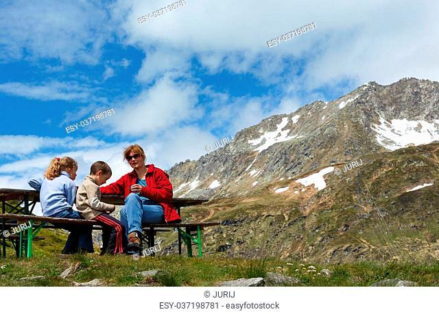 Family (mother with children) rest on summer Alps mountain plateau (Switzerland, Passo del San Gottardo)