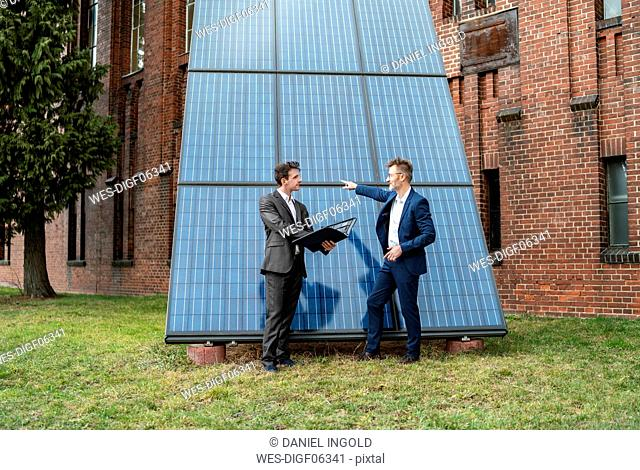 Two businessmen talking outside brick building at solar panels