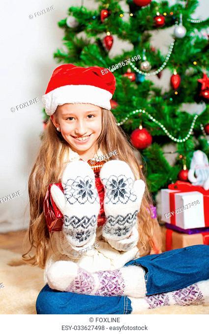 Little girl with long hair near a Christmas tree