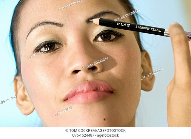 Asian model applying eyebrow pencil in studio setting