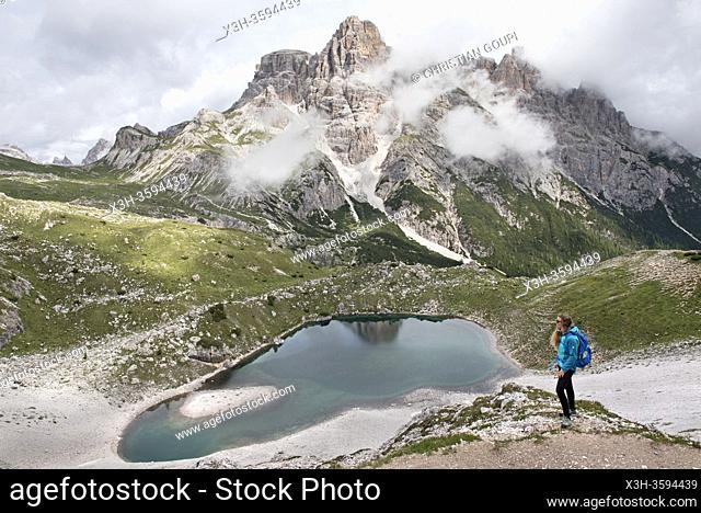 randonneuse sur un chemin en surplomd du Lago dei Piani inferiore , Parc naturel des Tre Cime (Drei Zinnen), Dobbiaco, Region du Trentin-Haut-Adige