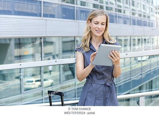 Smiling blond businesswoman using tablet