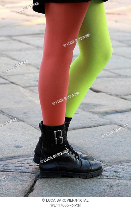 Legs of a girl with a red sock and one green