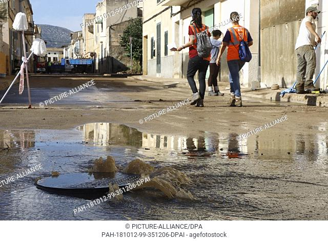 12 October 2018, Spain, Sant Llorenc: Neighbours and volunteers cleaning the village of Sant Llorenc three days after the flood disaster