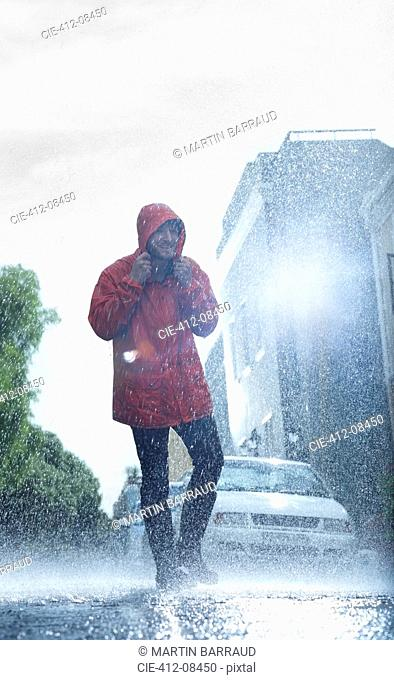 Man in raincoat walking in rainy street