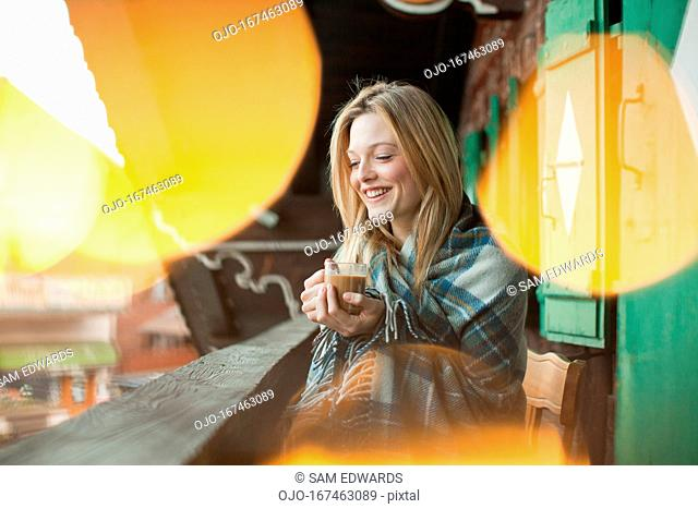 Smiling woman wrapped in a blanket and drinking coffee on cabin porch