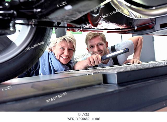 Portrait of smiling car mechanic with client in workshop at car