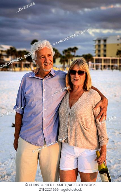 Retired couple enjoy a romantic walk on Siesta Key beach at sunset - MR