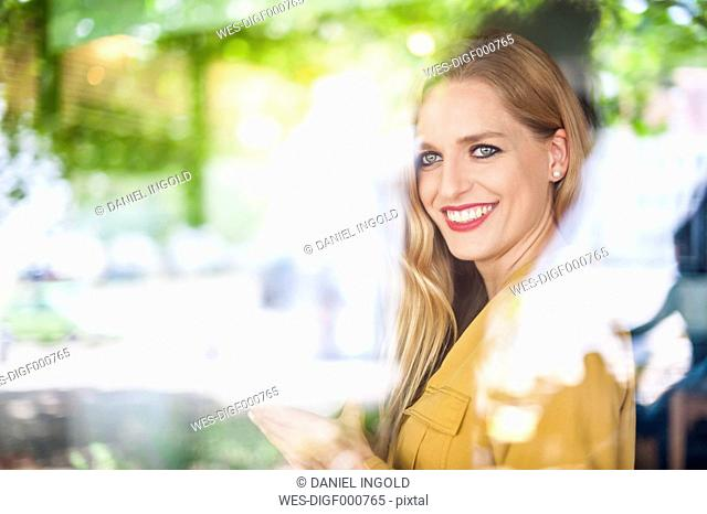 Portrait of smiling woman sitting behind window in a coffee shop