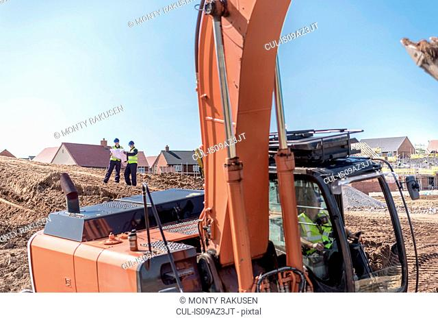 Excavator and builders on housing building site