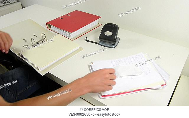 Man, sitting behind his desk at home, taking care of his personal administration, and filing bills, receipts and documents in to a binder