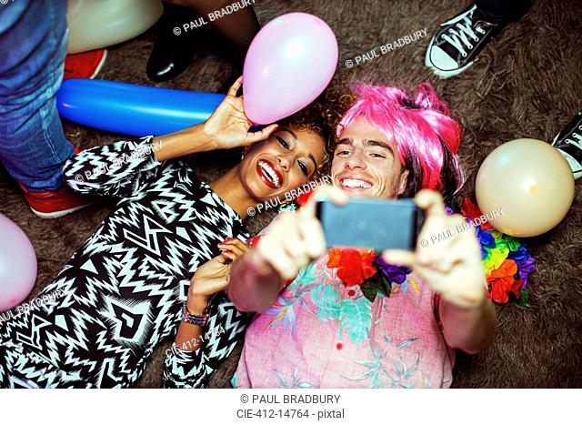 Couple taking self-portrait with cell phone on floor at party