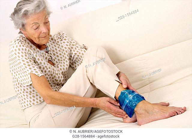 Senior woman applying a cold or hot gel compress on her ankle to soothe pain