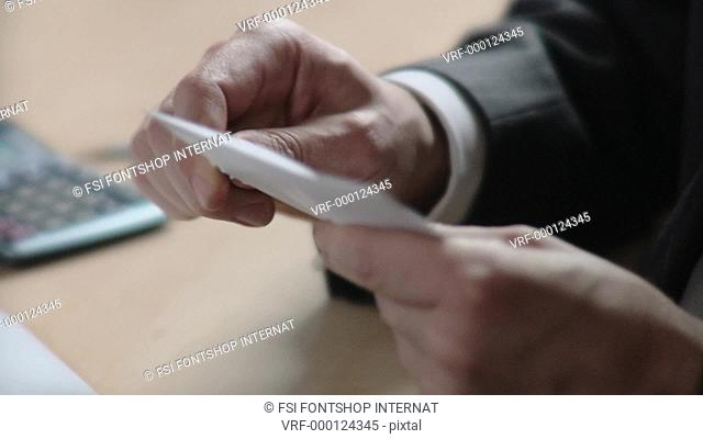 ECU, SELECTIVE FOCUS, Businessman opening mail at desk, close-up of hands