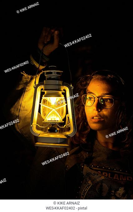 Young woman holding storm lantern in the dark