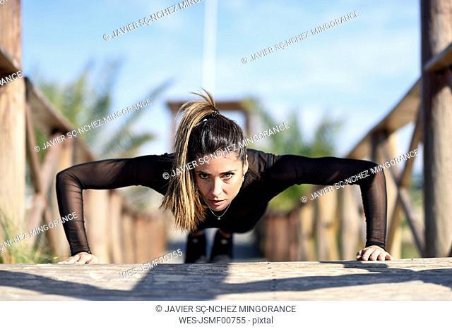 Sportive woman doing push-ups on wooden bridge