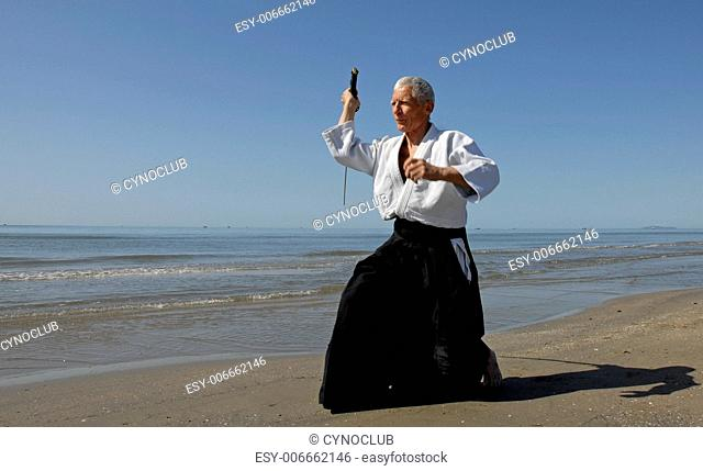 one old man are training in Aikido on the beach