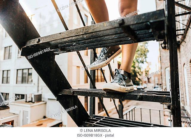 Woman climbing fire escape ladder of apartment building, Boston, MA, USA