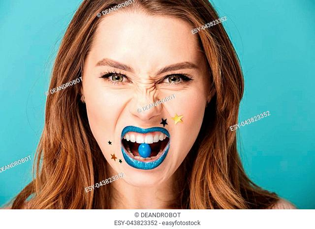 Portrait of an angry brown haired woman with bright sparkling makeup eating blue candy isolated over blue background