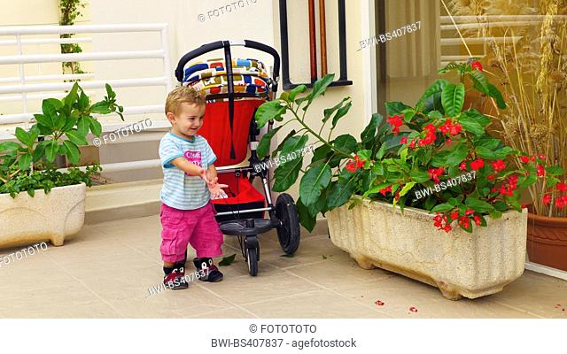 little boy standing in front of a buggy