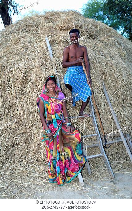 Couplestanding in front of haystack, BHAINA TRIBE, Soniyapath village, Jhangir Chapa dist, Chattisgarh, India