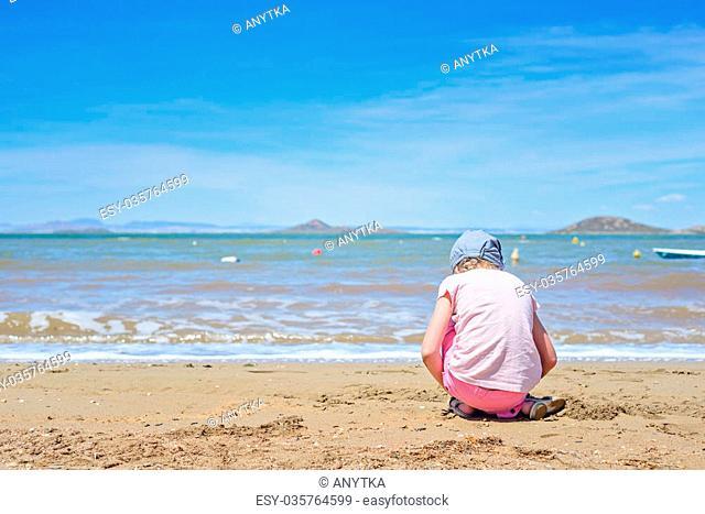 Little girl playing on the sandy Mar Menor beach, Spain