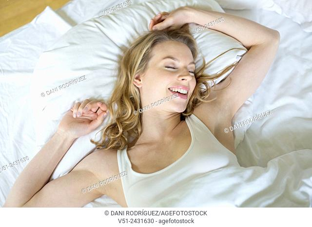 Pretty blonde woman waking up and stretching in bed
