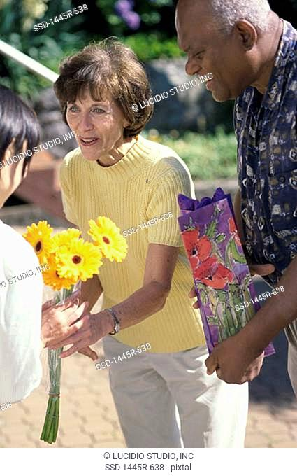 Mid adult couple giving flowers to a mid adult woman