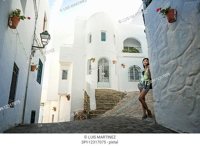 A Chinese young woman standing against a white residential building in Mojacar's downtown; Mojacar, Almeria, Spain